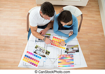 Young Couple Choosing Color From Swatch
