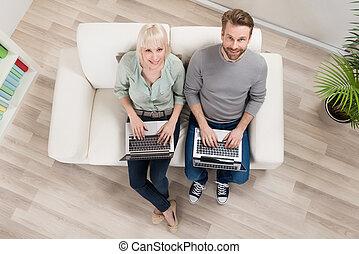 Couple Sitting On Sofa Using Laptop
