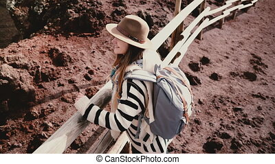 High angle view of young happy female tourist with backpack and arms wide open at the edge of Vesuvius volcano crater.