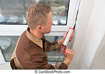 Man In Overall Applying Silicone Sealant - High Angle View...