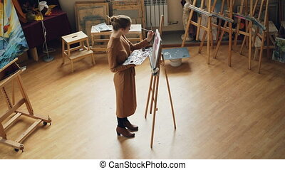 High angle view of young woman painter working in studio...