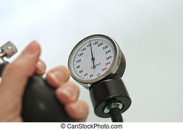 High Blood Pressure - Blood pressure gauge and a human hand...