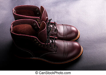High boots. Fashionable mens leather brown shoes on light  black background. Back view. Copy space.