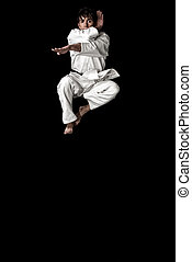 High Contrast karate young male fighter jump on black background.