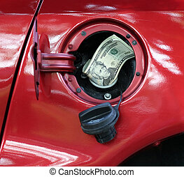 Twenty dollar bills sticking out of automobile gas tank illustrating the high cost of gas.