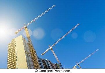 High cranes on the construction of residential buildings, against the blue sky.