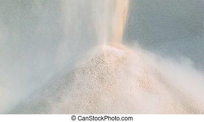 Machine pours pile of granite gravel