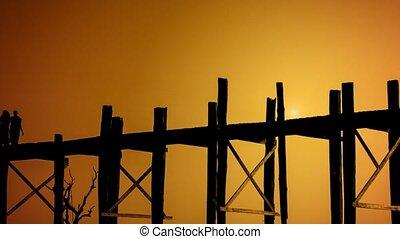 Monks walk through the ancient wooden bridge. Burma,...