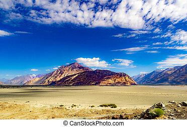 High dynamic range image of barren mountain in a desert with deep blue sky and white patchy clouds in ladakh, Jammu and Kashmir, India
