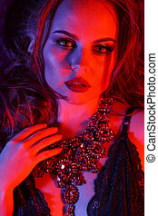 High Fashion girl model with trendy make-up in colorful bright lights. Woman portrait in red and blue colors.