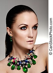 High fashion look. glamor closeup portrait of beautiful sexy brunette Caucasian young woman model with healthy hair, bright makeup, with perfect clean skin with green accessory jewelery