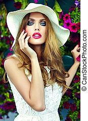 High fashion look. glamor closeup portrait of beautiful sexy stylish blond young woman model with bright makeup and pink lips with perfect clean skin in hat near summer flowers