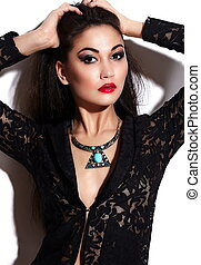 High fashion look. glamor closeup portrait of beautiful sexy stylish brunette Caucasian young woman model with bright makeup, with red lips, with perfect clean skin with jewelery in black cloth