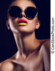 High fashion look. glamor closeup portrait of beautiful sexy stylish mode in sun glasses with bright colorful lips with perfect clean skin in studio