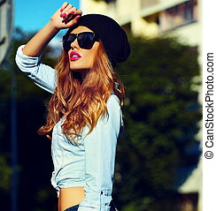High fashion look. glamor lifestyle blond woman girl model in casual jeans shorts cloth outdoors in the street in black cap in glasses