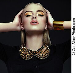 High fashion look.glamor closeup portrait of beautiful sexy stylish blond young woman model with bright yellow makeup with perfect clean skin with gold jewelery in black cloth