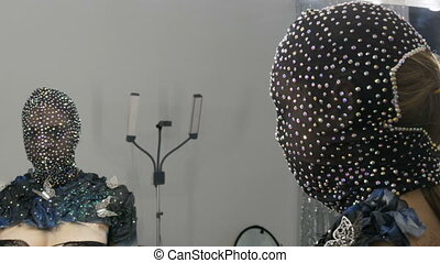 High-fashion. Model in the image of an alien girl in a black mask in sparkling rhinestones, sparkles, metal butterflies on a black and silver background posing at studio front of mirror