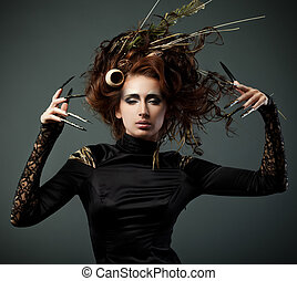 High fashion model in black dress, with long nails and...