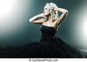 High fashion woman in sexy pose and  large formal dress