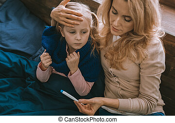 Nice serious woman holding her daughters forehead