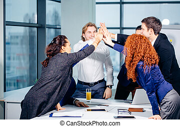 High-five. young business people giving high-five on meeting in office