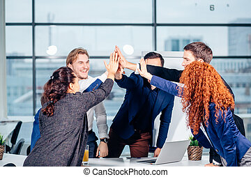 High-five. young business people giving high-five on meeting...