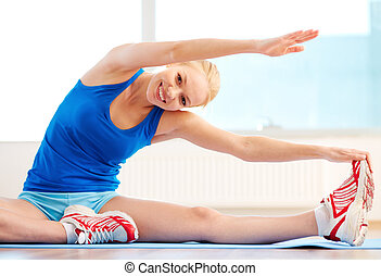 Smiling woman with high body flexibility exercising in the gym