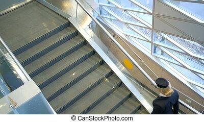 High flight attendant, shod in high heels, climbs up the...