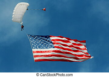 American flag flying high attached to a skydiver