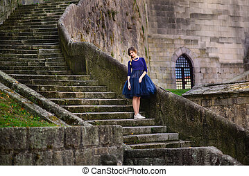 girl posing in blue dress standing on stone stairs