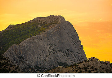 high gray mountain with a flat slope covered with greenery in orange yellow light dawn of the sun