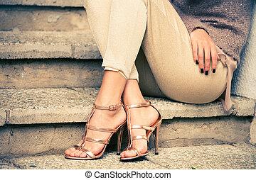 high heels - woman legs in high heel golden sandals sit on...