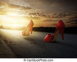 A pair of high heels walking down a road at sunset.