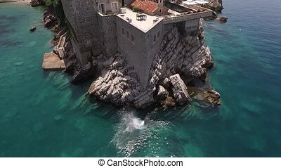 The guy jumps into the water from a great height from wall of Sveti Stefan Island in Montenegro.