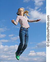 Young girl trying to jump above the clouds
