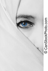 High key portrait of a woman with empty expression on her face hijab and blue eye