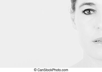 High key portrait of a woman with only half of her face
