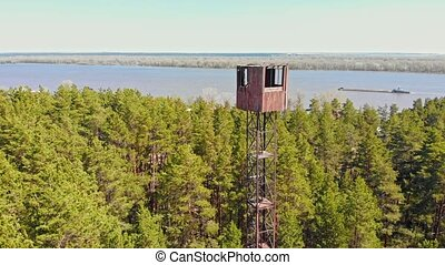 High landmark tower building in the forest - a barge sails on the background. Aerial shot
