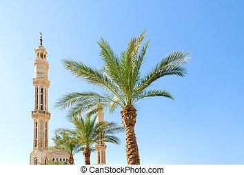 high mosque and green palm trees against a clear blue sky in Sharm El Sheikh