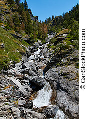 High mountain stream flowing between the rocks