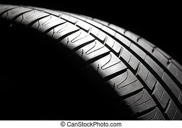 Modern high-performance sport summer tire close-up in a low key. Studio shot.