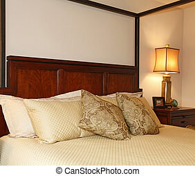 High posts bed with a beautiful beige bedding. Close up view.