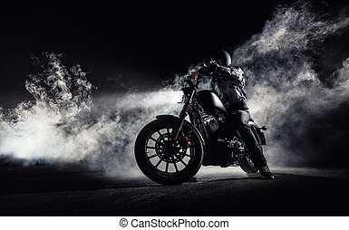 High power motorcycle chopper with man rider at night. Fog...