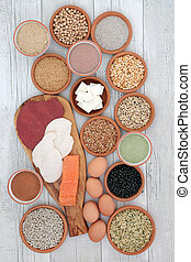 High protein food selection with meat, fish, vegan tofu, legumes, dairy, supplement powders, grains and seeds. Hgh in dietary fibre, antioxidants and vitamins. Top view on rustic wood background.
