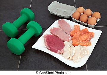 High protein food for body builders of lean steak, pork, chicken, salmon and eggs with dumbbell weights on marble background.
