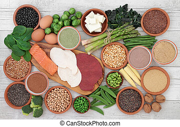 High protein food sampler with fresh vegetables, meat, fish, tofu, legumes, nuts, supplement powders, grains and seeds. High in dietary fibre, antioxidants and vitamins. Top view.