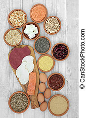 High protein food with meat, fish, dairy, vegan tofu, legumes, grains and seeds, high in dietary fibre, antioxidants, anthocaynins and vitamins. Top view on rustic wood background.