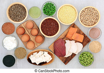High protein health food concept with dairy, legumes, bean curd, vegetables, grains, supplement powders and seeds. Foods high in dietary fibre, vitamins and antioxidants. Top view.
