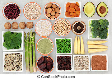 High protein source plant health food with fresh vegetables, legumes, dried fruits, nuts, supplement powders, grains and seeds on rustic white wood, high in dietary fibre, antioxidants and vitamins.
