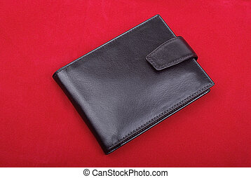 High quality black leather wallet isolated on red background. Studio shot.